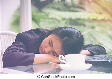 Business woman heavy workload sleep at office desk with...