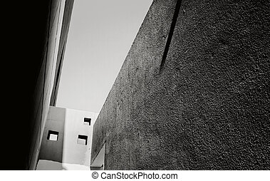 black-and-white view of the sky from a narrow passage between the houses