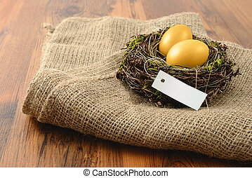 nest with golden eggs with lable copy space on wooden table...