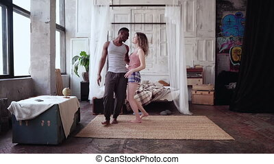 Multiethnic couple in pajamas having fun together. African...