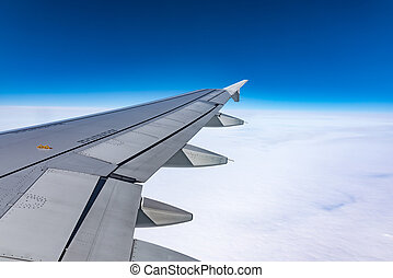 Wing of an airplane in the sky - View from the porthole of...