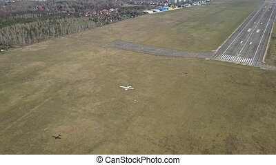 Small propeller aircraft flying near city airport runway -...