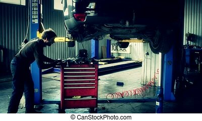mechanic push red tools box under lifted car.