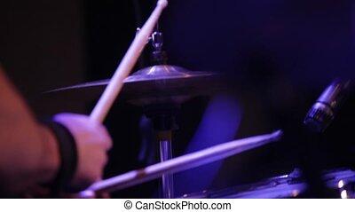 Man plays drums close-up.