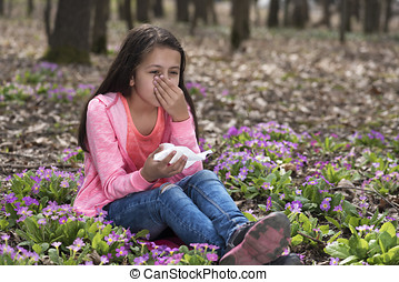 Girl sitting among primroses and sneezing. Selective focus