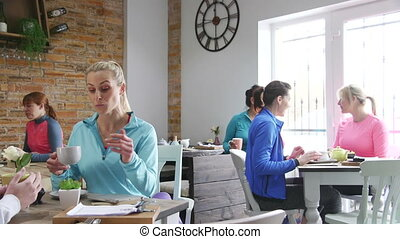 Catch Up Coffee - Women are in a cafe, socialising over tea...