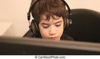 Young boy using computer and headphones - Young kid wearing...
