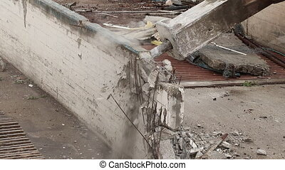 Wall demolition on construction site by bulldozer