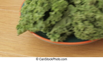Placing kale on wooden table - Plate with green fresh kale...