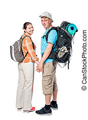 Happy couple with backpacks holding hands in studio on white background