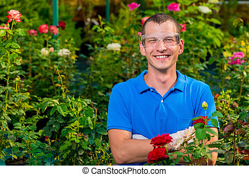 Happy man with glasses and laboratory gloves in a greenhouse among flowers