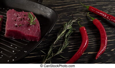 Beef fillet on a pan with pepper, rosemary and garlic. -...