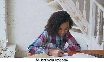 Teenage curly haired mixed race young girl sitting at the...