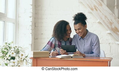 Two attractive curly haired mixed race young girls sitting at the table have fun while learning lessons and using tablet at home