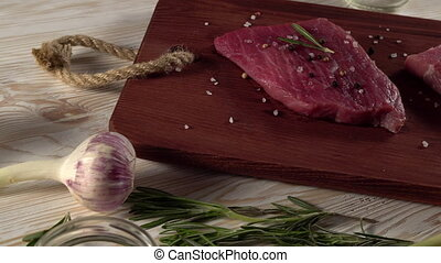 Beef fillet on a desk with pepper, rosemary axe and garlic....