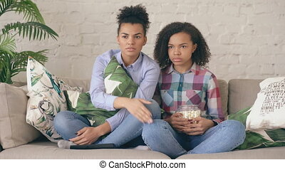 Two mixed race curly girl friends sitting on the couch and watch nervous TV show and eat popcorn at home