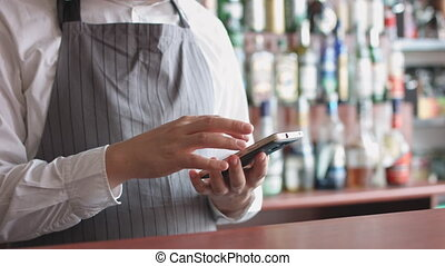 Bartender with mobile phone - Cropped shot of bartender in...
