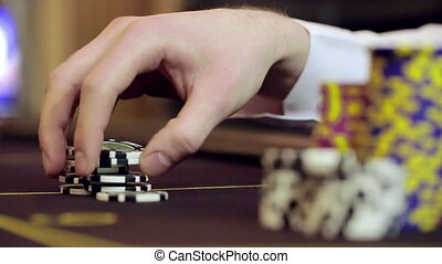 Casino: Man playing poker, excited, turns casino tokens in...
