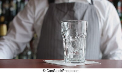 Bartender preparing cocktail with ice and lime - Front view...