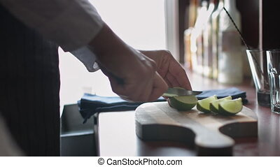 Bartender cutting limes for cocktails