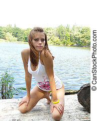 girl at lake - young girl sunbathes on the wooden bridge