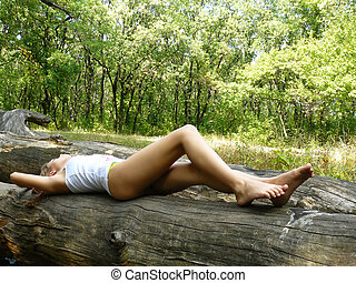 girl dreams on a log in wood - seminude girl has a rest on a...