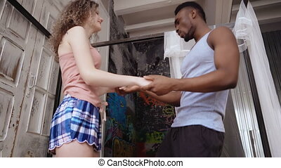 Beautiful multiracial couple dancing on bed. African man and...
