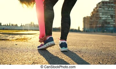 Running shoes - woman tying shoe laces and running outdoors....