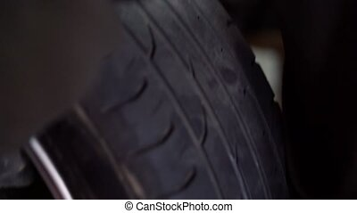 Car wheel with tire rotating closeup