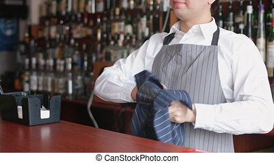 Bartender wiping glass with rag - Bartender wiping glasses...