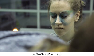 Makeup artist paints eye shadows on brown long-haired model in studio