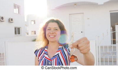 Attractive young woman holding keys while standing outdoor against new house.
