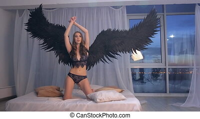 Model with black wings in lingerie on photo shoot inside studio