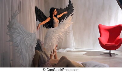 Studio shooting of two models blond and brunette angels with wings