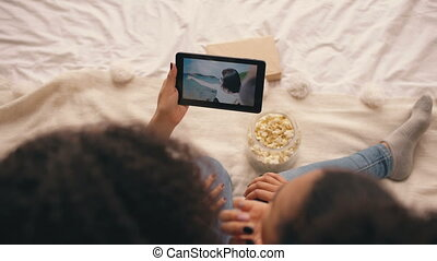 Top view of two girlfriends sitting on bed at home talking on skype on tablet computer with their friend having vacation on beach