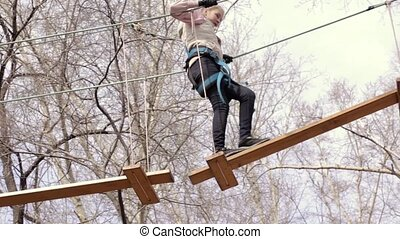 Young teenager climber walks by pendant log bridge on high...