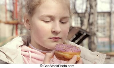 teenager girl eating a donut in an outdoor park