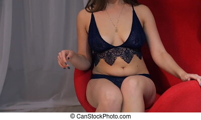 Plus size model in lingerie on red chair photo session...
