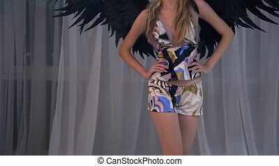 Figure of model in night costume with black wings on photo shoot