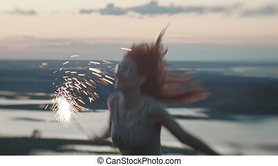 Smiling young woman dancing on a high hill with sparkler at dusk, close up