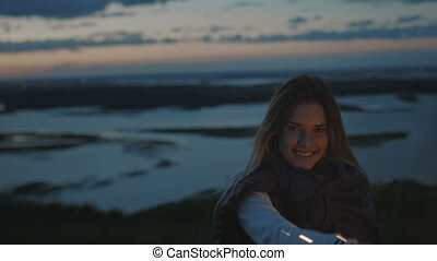 Smiling young woman stands on a high hill with sparkler at sunset in slow motion