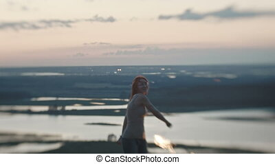 Smiling young woman on a high hill waving a Sparkler at dusk...