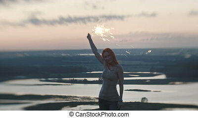 Smiling young woman standing on a high hill with sparkler at dusk