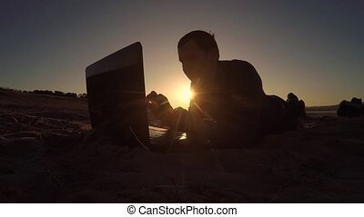 man laptop. businessman freelancer man laptop working behind sitting on beach freelancing silhouette in the sun