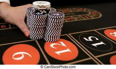 Croupier moves chips on table at casino.