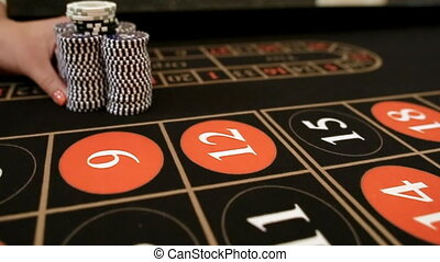 Croupier moves chips on table at casino