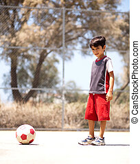 Young player ready to play soccer, outdoors
