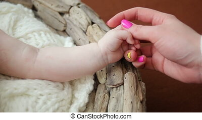 mother holds hand of his little daughter lying in a...