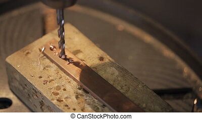 The machine drills platinum metal brass for electrical...