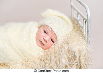 Kid resting covered with yellowish cover sheet - Small kid...